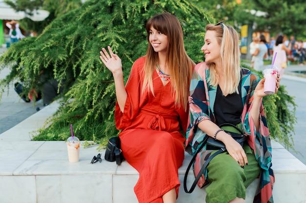 Dwie uśmiechnięte kobiety rozmawiają i spędzają czas razem w słonecznym nowoczesnym mieście