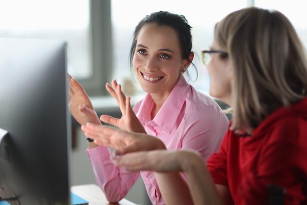 Dwie uśmiechnięte kobiety siedzą przy komputerowej koncepcji kursów edukacyjnych