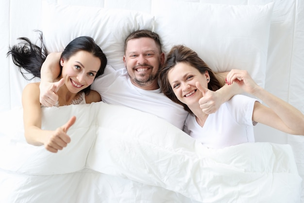 Dwie uśmiechnięte kobiety z mężczyzną leżą w łóżku i trzymają kciuki do góry