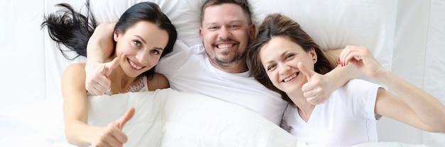 Dwie uśmiechnięte kobiety z mężczyzną leżą w łóżku i trzymają kciuki w górę poligamicznej koncepcji związku