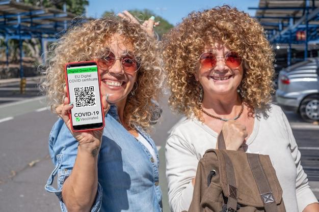 Dwie uśmiechnięte, kręcone kobiety gotowe do podróży, trzymające telefon komórkowy z cyfrowym zaświadczeniem o szczepieniu covid 19