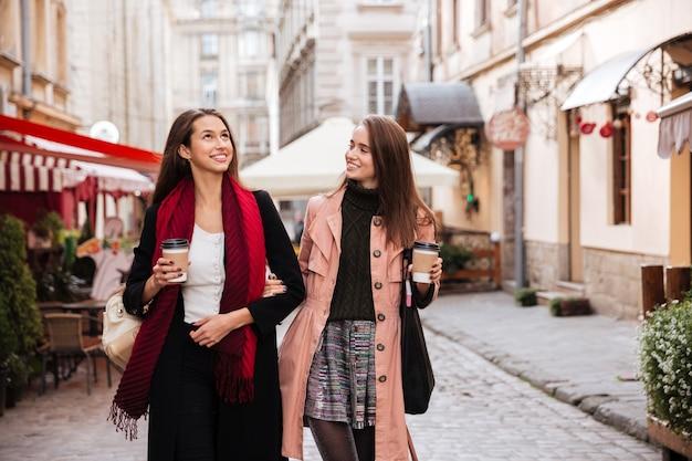 Dwie uśmiechnięte ładne młode kobiety spacerujące i pijące kawę na starym mieście