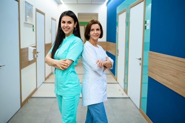 Dwie uśmiechnięte lekarki w mundurze pozuje na korytarzu kliniki. profesjonalny specjalista medyczny w szpitalu, laryngolog lub otolaryngolog, ginekolog lub mammolog, chirurg