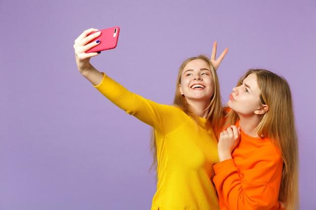 Dwie uśmiechnięte młode blond bliźniaczki siostry dziewczyny w kolorowe ubrania robi selfie nakręcony na telefon komórkowy na białym tle na pastelowej fioletowej niebieskiej ścianie. koncepcja życia rodzinnego osób.