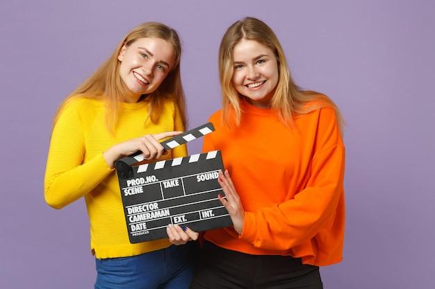 Dwie uśmiechnięte młode blond bliźniaczki siostry dziewczyny w kolorowe ubrania, trzymając klasyczny czarny film, co clapperboard na fioletowej niebieskiej ścianie. koncepcja życia rodzinnego osób. .