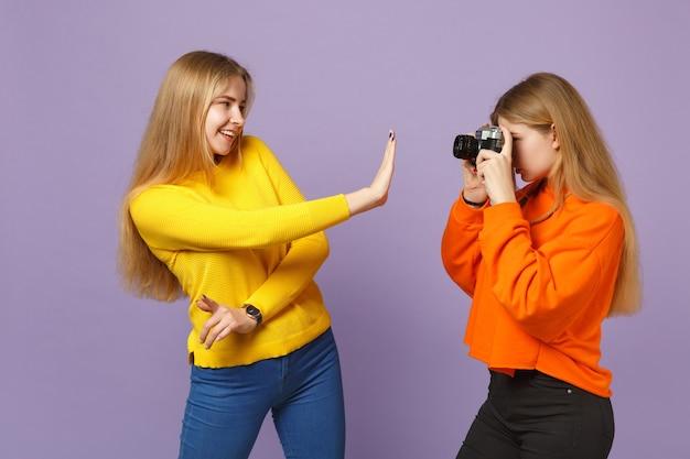 Dwie uśmiechnięte młode blond siostry bliźniaczki siostry dziewczyny w kolorowe ubrania robiące zdjęcia na retro vintage aparat fotograficzny na białym tle na fioletowej niebieskiej ścianie. koncepcja życia rodzinnego osób.