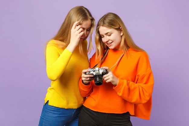 Dwie uśmiechnięte młode blondynki bliźniaczki siostry dziewczyny w żywe kolorowe ubrania, trzymając aparat retro vintage na białym tle na fioletowej niebieskiej ścianie. koncepcja życia rodzinnego osób.