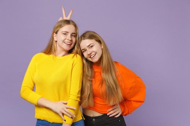 Dwie uśmiechnięte młode blondynki bliźniaczki siostry dziewczyny w żywych, kolorowych ubraniach bawią się, na białym tle na pastelowej fioletowej niebieskiej ścianie. koncepcja życia rodzinnego osób.