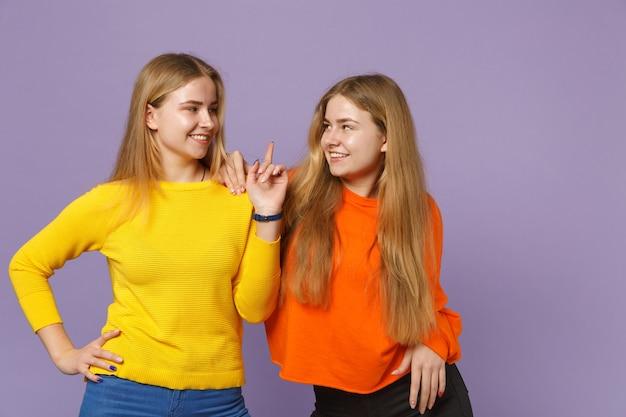 Dwie uśmiechnięte młode blondynki siostry bliźniaczki dziewczyny w kolorowych ubraniach, patrząc na siebie, wskazując palcem wskazującym w górę, na białym tle na fioletowej niebieskiej ścianie. koncepcja życia rodzinnego osób.