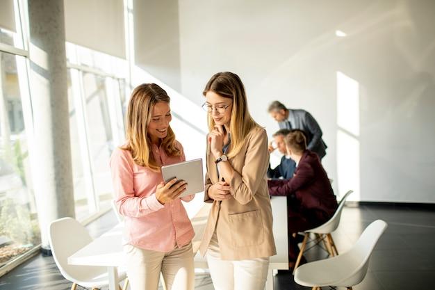 Dwie uśmiechnięte młode kobiety, patrząc na cyfrowy tablet w biurze