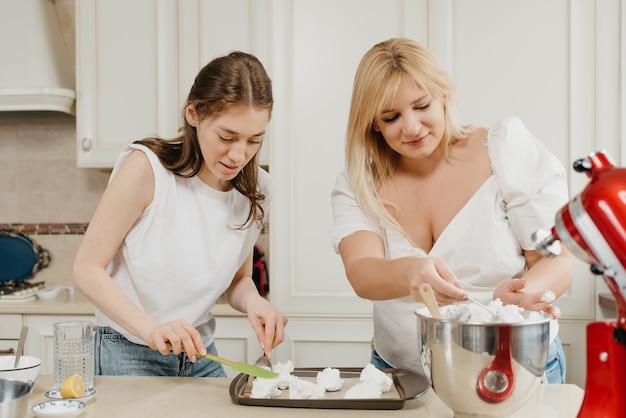 Dwie uśmiechnięte młode kobiety pilnie stawiają bitą bezę na tacy z łyżką i łopatką w kuchni