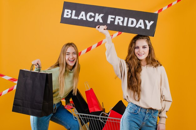 Dwie uśmiechnięte młode piękne kobiety mają czarny piątek znak i wózek z kolorowymi torbami na zakupy i taśmą sygnałową izolowanych na żółtym