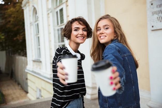 Dwie uśmiechnięte nastolatki opiekania okulary przeciwsłoneczne