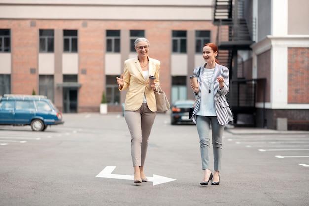 Dwie uśmiechnięte panie. dwie stylowe uśmiechnięte panie z papierowymi kubkami kawy uśmiechają się podczas wspólnego spaceru na świeżym powietrzu