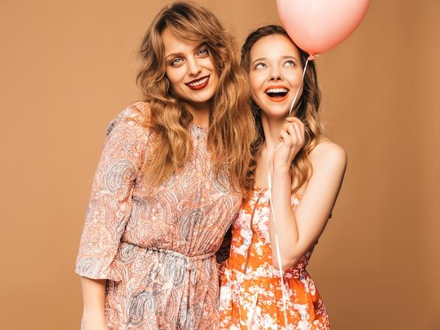 Dwie uśmiechnięte piękne kobiety w letnich sukienkach. girls posing. modele z kolorowymi balonami. zabawy, gotowe na uroczystości urodzinowe lub przyjęcie świąteczne
