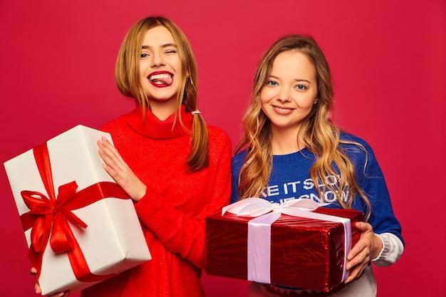 Dwie uśmiechnięte piękne kobiety w stylowych swetrach z dużymi pudełkami prezentowymi