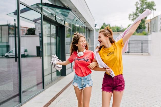 Dwie uśmiechnięte przyjaciółki idą na zakupy w letni poranek i opowiadają sobie zabawne historie