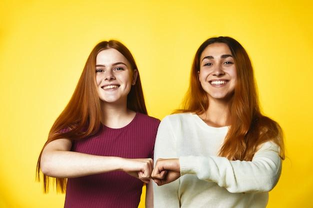 Dwie uśmiechnięte rudowłosy dziewczynki stoją ramię w ramię, a ich pięści są razem, na żółtym ubraniu w zwykłe ubrania