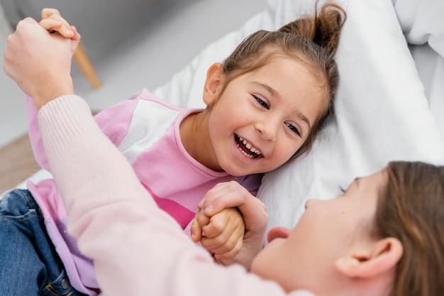 Dwie Uśmiechnięte Siostry Bawiące Się Razem W Domu Premium Zdjęcia