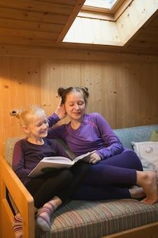 Dwie uśmiechnięte siostry, które czytają książkę w twoim pokoju