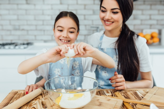Dwie uśmiechnięte siostry z jajkami gotują w kuchni