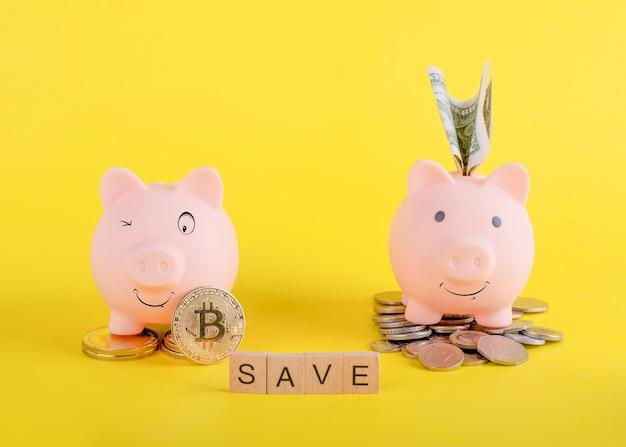 Dwie uśmiechnięte skarbonki z pieniędzmi, bitcoinami i tytułem oszczędzają na żółtym tle