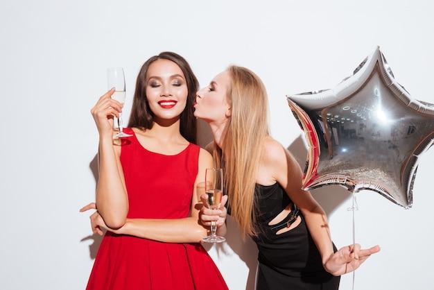 Dwie uśmiechnięte śliczne młode kobiety pijące szampana i całujące się na białym tle