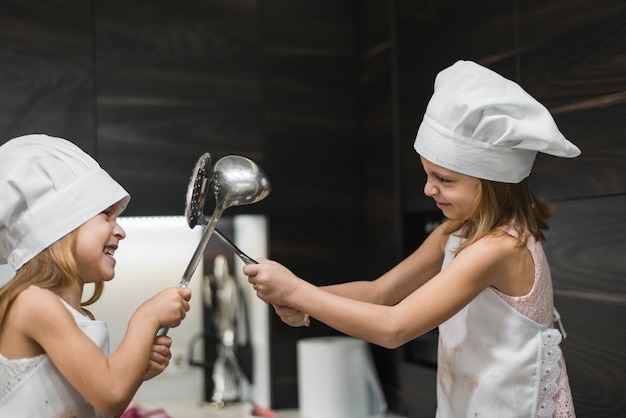 Dwie uśmiechnięte słodkie siostry w czapkach szefa kuchni walczą z naczynia kuchenne