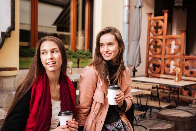 Dwie uśmiechnięte, urocze młode kobiety siedzące i pijące kawę na starym mieście