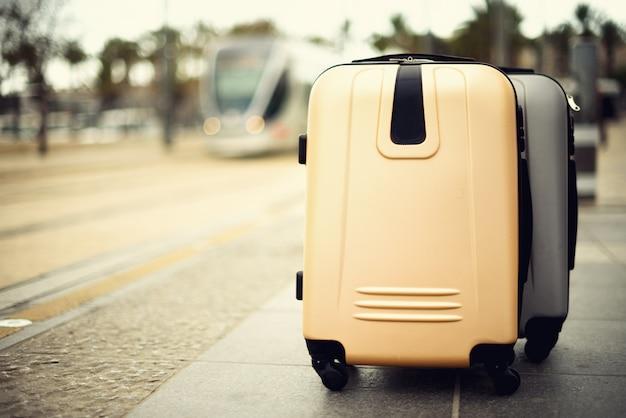 Dwie walizki stojące na stacji kolejowej przed pociągiem miejskim.