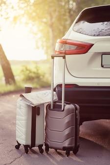 Dwie walizki w pobliżu samochodu na drodze podczas podróży