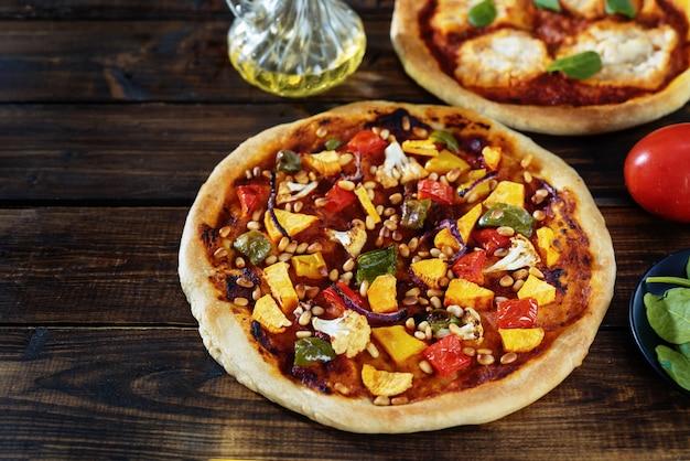 Dwie wegańskie pizze na ciemnym tle rustykalnym