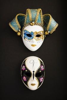 Dwie weneckie maski karnawałowe na czarnej powierzchni. lokalizacja pionowa.