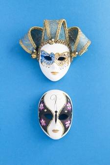 Dwie weneckie maski karnawałowe na niebieskiej powierzchni. widok z góry. lokalizacja w pionie.