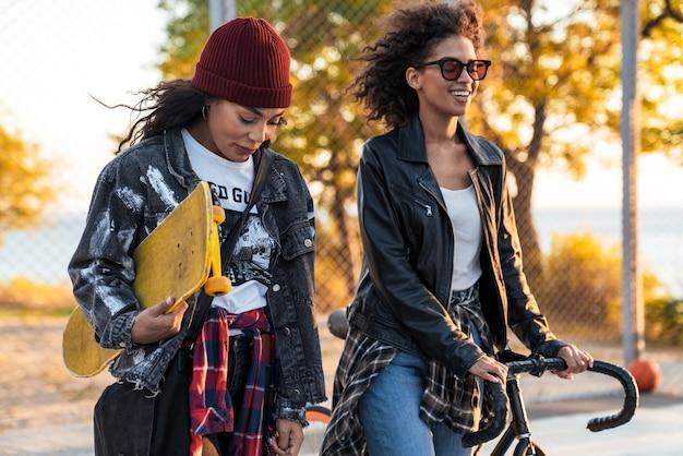 Dwie wesołe, atrakcyjne młode afrykańskie dziewczyny stojące na boisku sportowym z rowerem i deskorolką