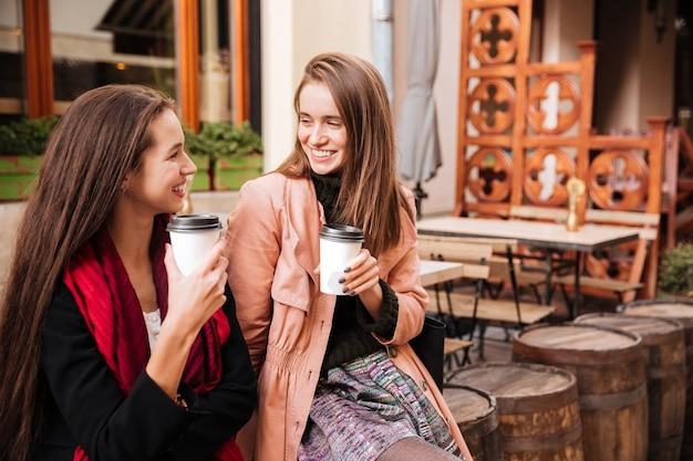 Dwie wesołe, atrakcyjne młode kobiety rozmawiające i pijące kawę na starym mieście
