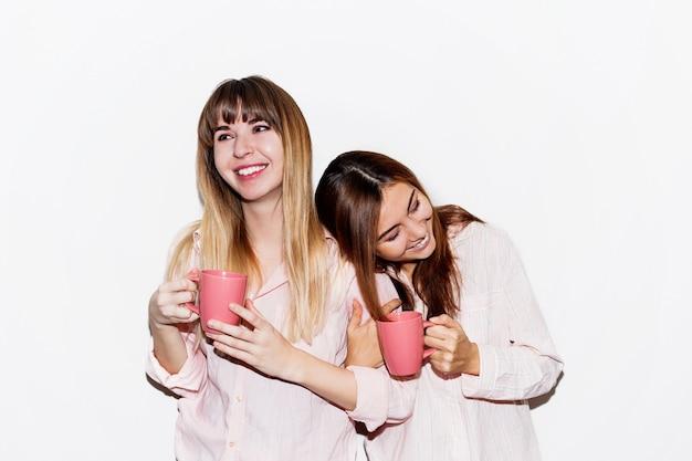 Dwie wesołe białe kobiety w różowej piżamie ze stawianiem filiżanki herbaty. portret z lampą błyskową.