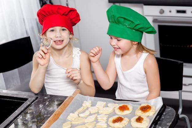 Dwie wesołe dziewczynki gotują w kolorowych czapkach, przygotowują ciasto