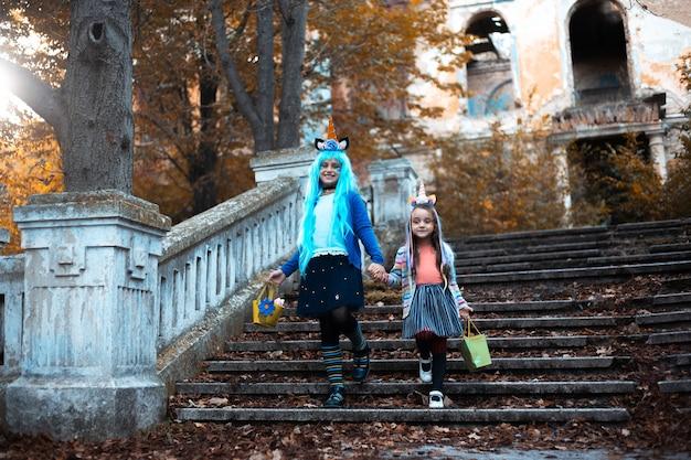 Dwie wesołe dziewczynki w kolorowych kostiumach jednorożca na halloween