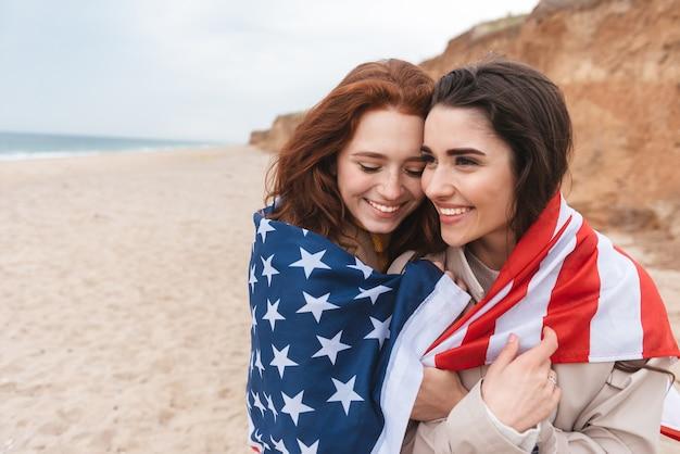 Dwie wesołe dziewczyny biegające po plaży niosące amerykańską flagę