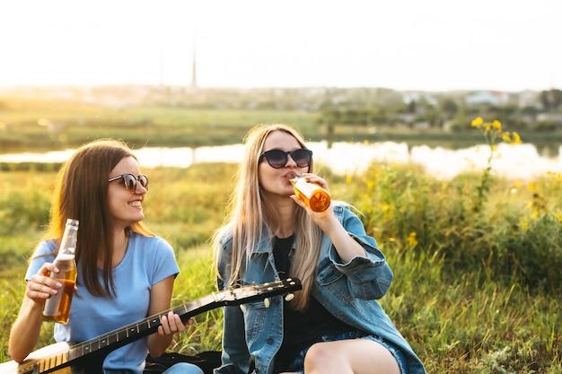 Dwie wesołe dziewczyny i młodzi przyjaciele w okularach przeciwsłonecznych, pijący piwo i cieszący się razem spędzonym razem o zachodzie słońca.