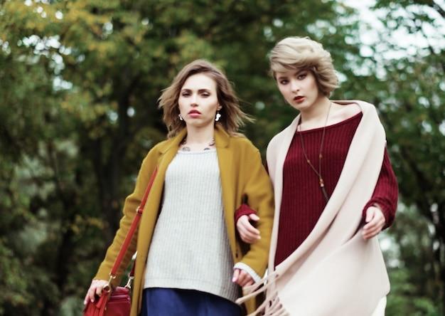Dwie wesołe dziewczyny modowe w jesiennym parku
