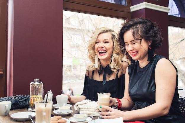 Dwie wesołe dziewczyny siedzą przy stoliku w kawiarni i piją drinki.