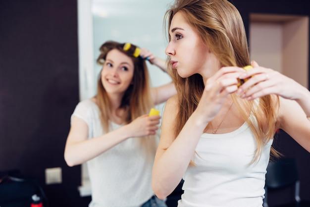 Dwie wesołe dziewczyny układające włosy w lokówkach w domu