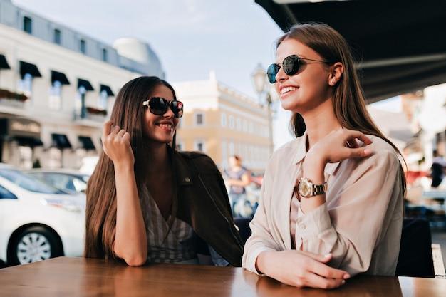 Dwie wesołe dziewczyny w okularach przeciwsłonecznych szczęśliwie rozmawiają ze sobą z idealnymi uśmiechami w okularach przeciwsłonecznych na placu.