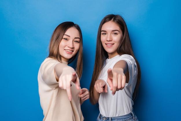 Dwie wesołe eleganckie dziewczyny, uśmiechając się i wskazując, co oznacza hej ty na białym tle na niebieskiej ścianie