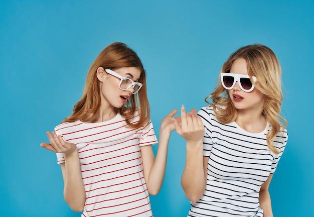 Dwie wesołe kobiety w pasiastych koszulkach w letnim stylu na niebieskim tle