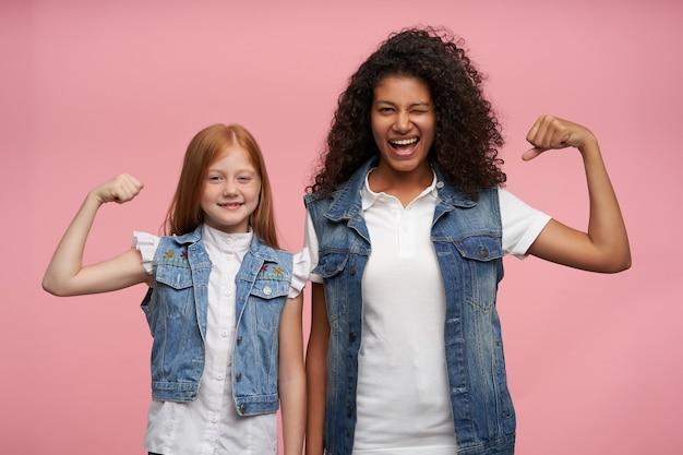 Dwie wesołe, ładne młode panie stojące na tle różu z podniesionymi rękami i radośnie demonstrujące swoje silne bicepsy, ubrane w dżinsowe kamizelki i białe koszule