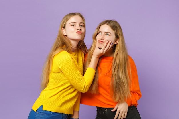 Dwie wesołe młode blond bliźniaczki siostry dziewczyny w żywych, kolorowych ubraniach bawią się, wygłupiając się na białym tle na pastelowej fioletowej niebieskiej ścianie. koncepcja życia rodzinnego osób.