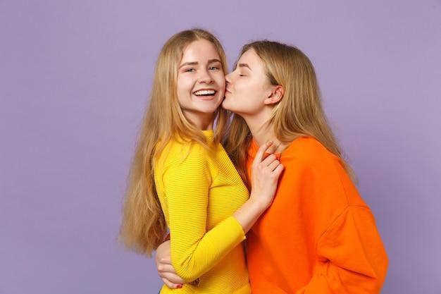 Dwie wesołe młode blond siostry bliźniaczki dziewczyny w żywych, kolorowych ubraniach, przytulanie, całowanie w policzek na białym tle na pastelowej fioletowej niebieskiej ścianie. koncepcja życia rodzinnego osób.